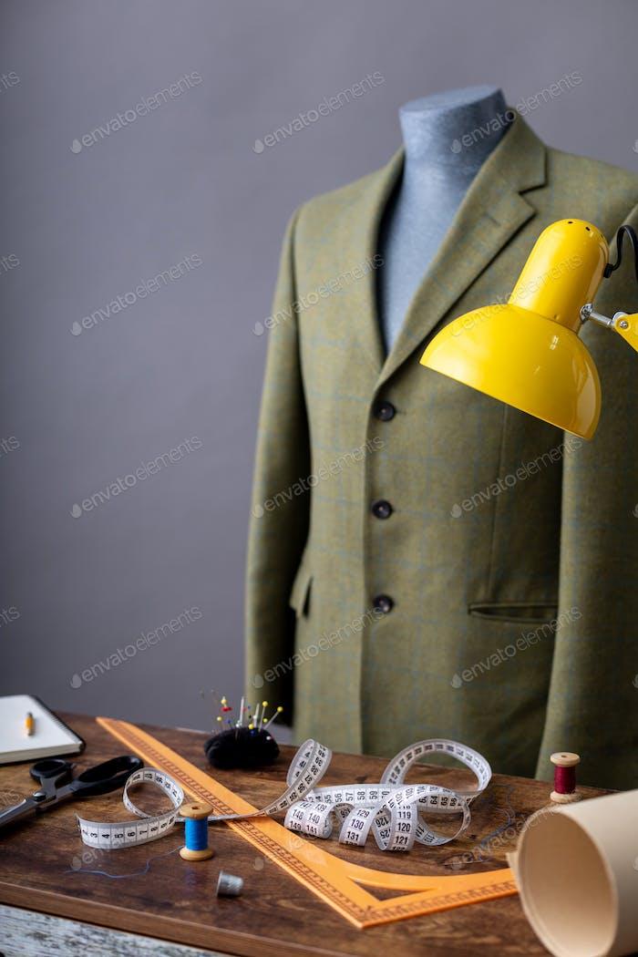 Anzugjacke auf männlicher Schneiderpuppe und Nähutensilien,