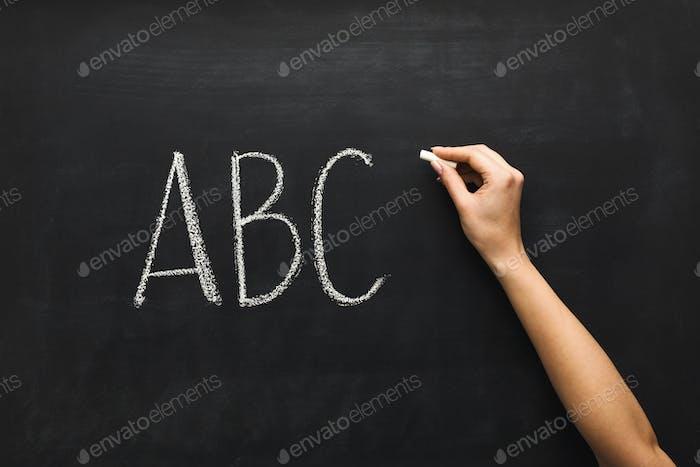 Woman writing abc on black chalkboard