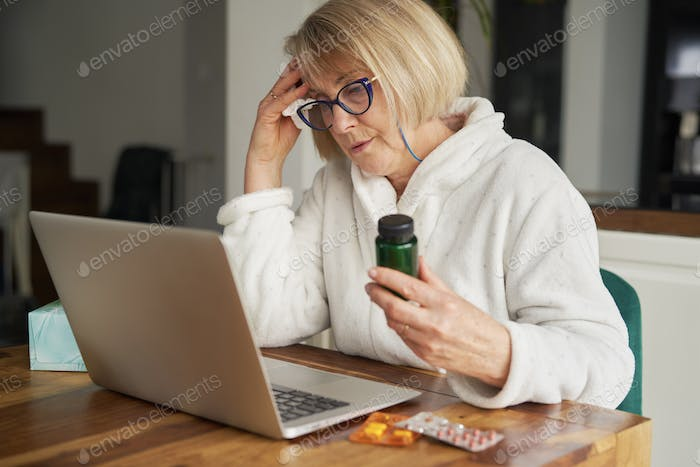 Senior woman showing medicine during online consultation at home