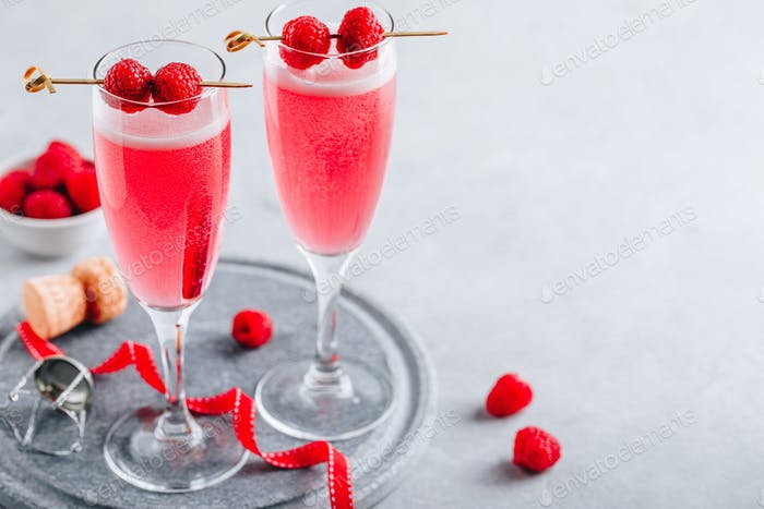 Pink cocktail with champagne or prosecco and fresh raspberries for  Valentine's day.