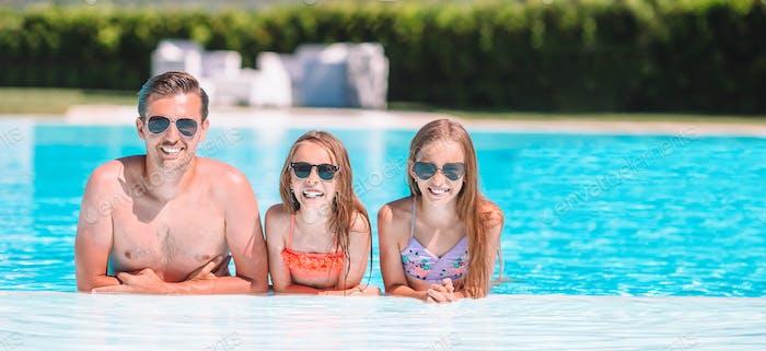 Glückliche Familie von drei im Freibad