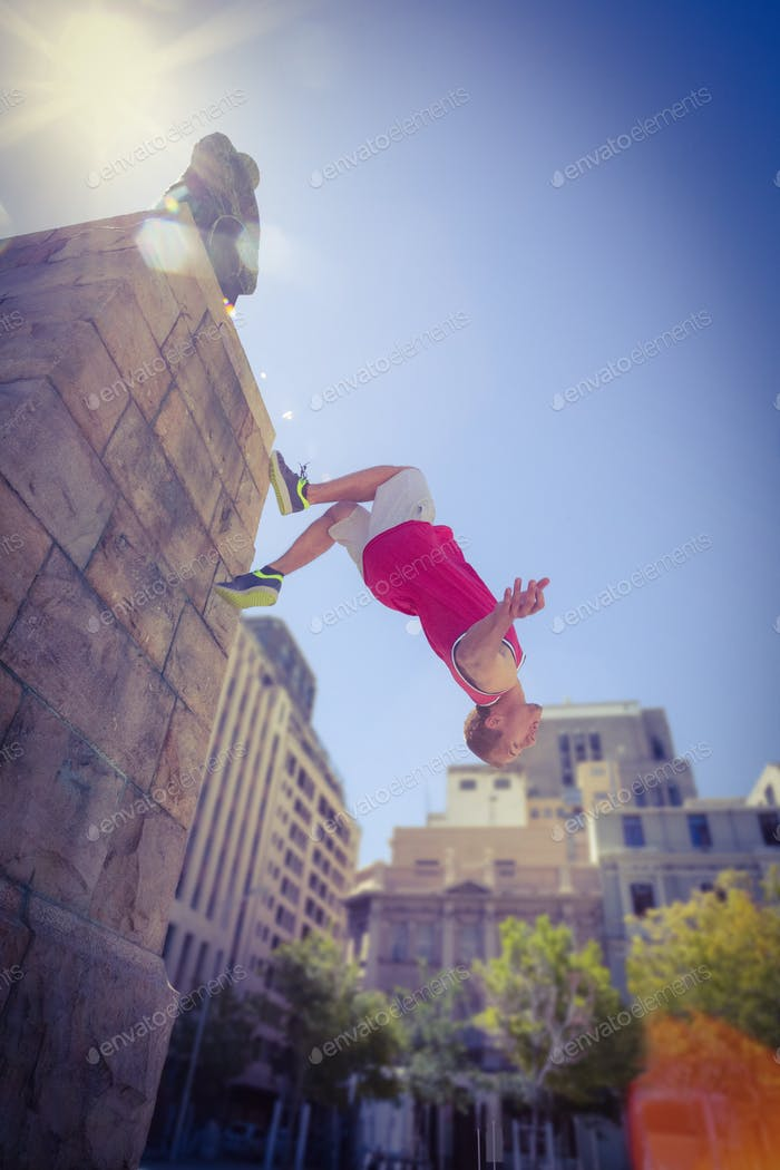 Happy man doing parkour on a sunny day