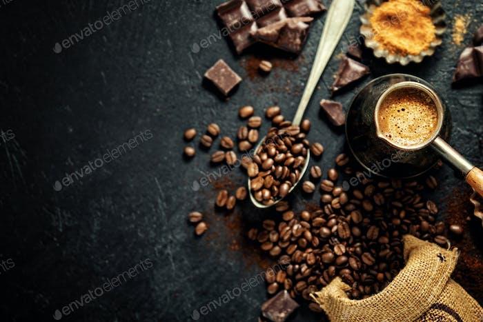 Kaffeebohnen mit Requisiten für die Kaffeezubereitung