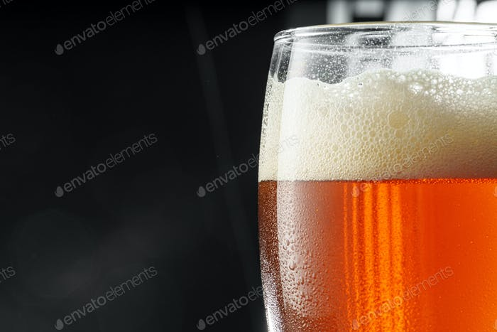 Glass of beer on black background, copy space