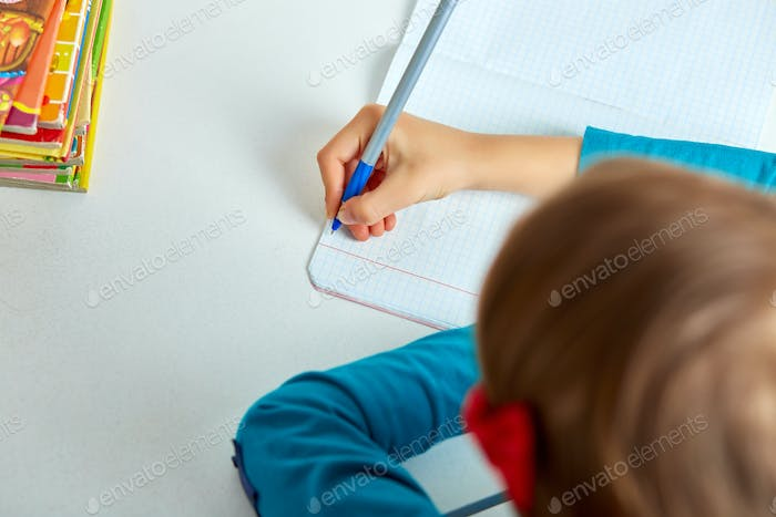 Schoolgirl doing homework, writing, studying lesson, coronavirus home school