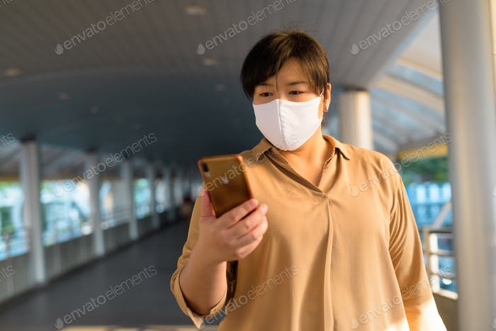 Overweight Asian woman with mask using phone in the city