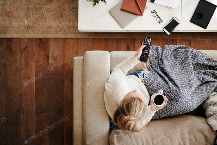 Overhead Shot Looking Down On Woman At Home Lying On Sofa Watching Television