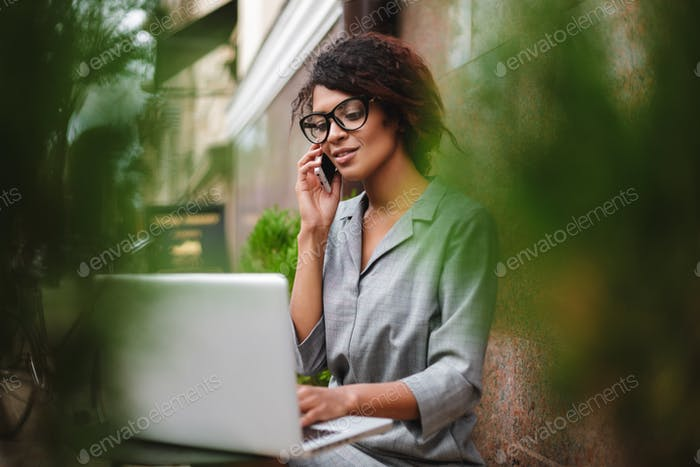 Young lady with dark curly hair sitting at table on street and working on laptop