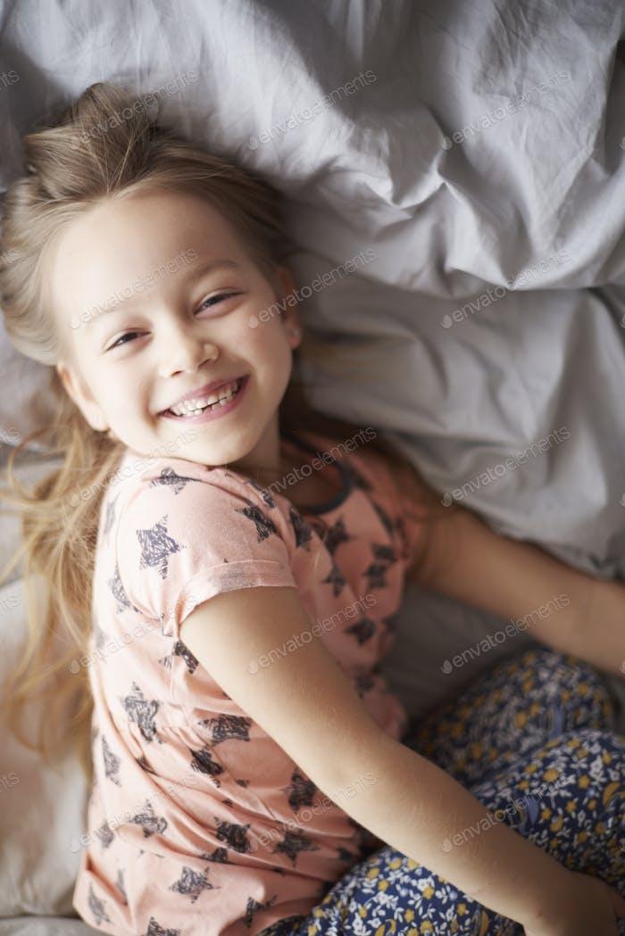 Happy girl in bed in the morning