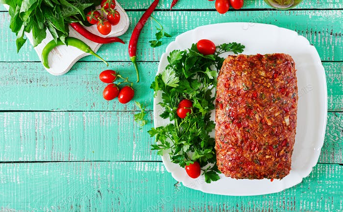 American food. Homemade ground beef meatloaf with ketchup and bell peppers.