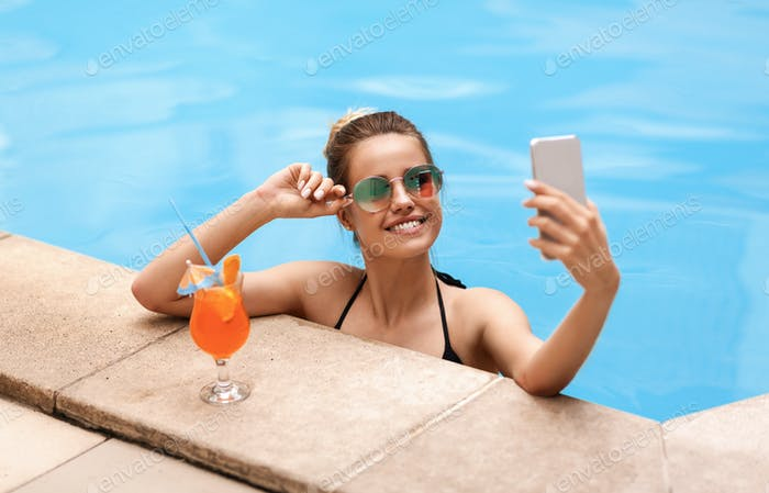 Schöne kaukasische Mädchen unter Selfie auf dem Smartphone im Pool im tropischen Resort
