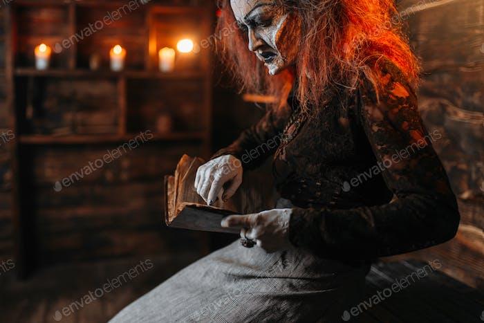 Gruselige Hexe liest Zauberbuch, spirituelle Seance
