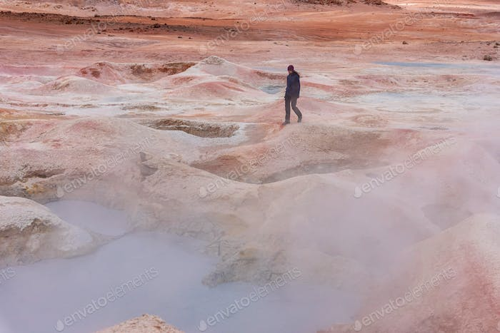 Woman with a camera walking through some mud pits with volcanic activity in the Andean Highlands