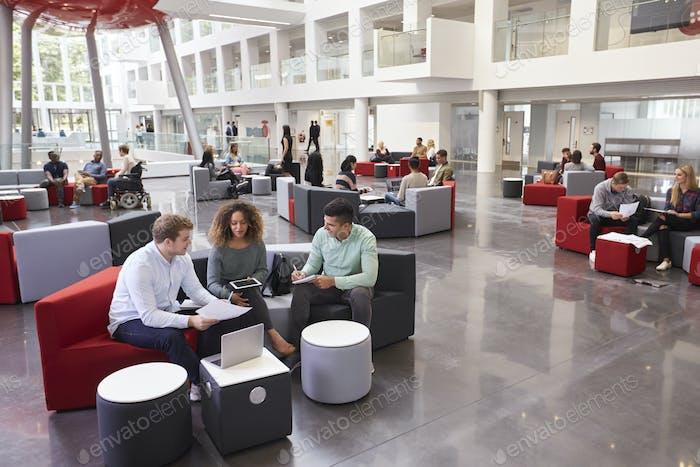 Students sitting in university atrium, three in foreground
