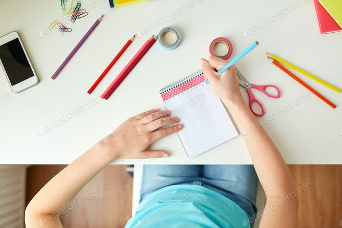 girl drawing in notebook at home