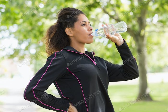 Side view of a tired healthy young woman drinking water in the park
