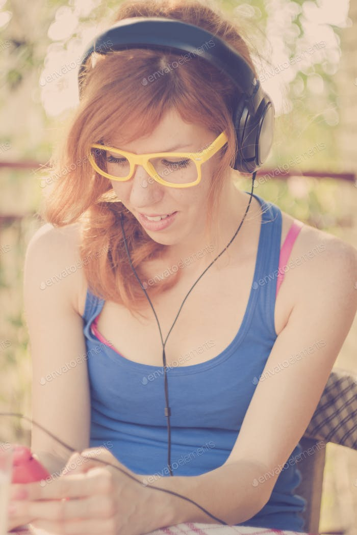 Beautiful hipster girl with headphones listening to the music