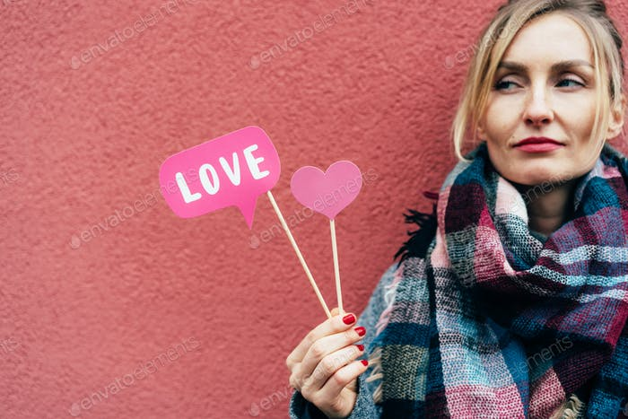 Young beautiful woman holds props love. Valentine's Day in February