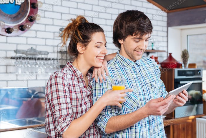 Happy couple drinking juice and using tablet on kitchen