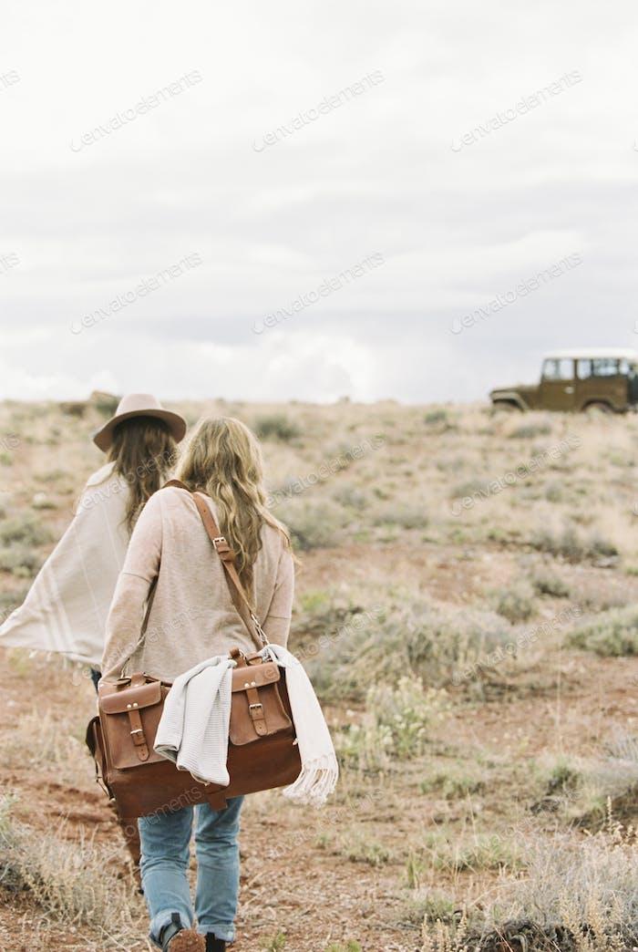 Two women walking towards a 4x4 parked