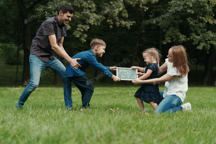 Four member family having fun while playing in the park