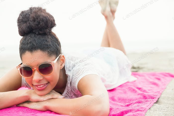 Smiling woman lying on towel at the beach