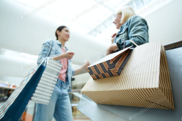 Colorful paper shopping bags in hands of customers