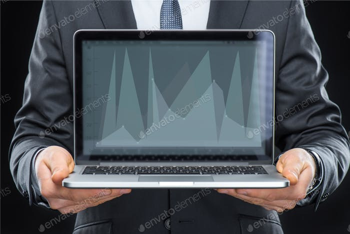 Businessman holding laptop computer with diagram on screen