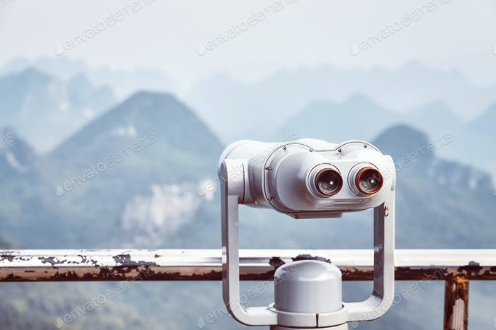 Vintage toned picture of tourist binoculars pointing at mountains.