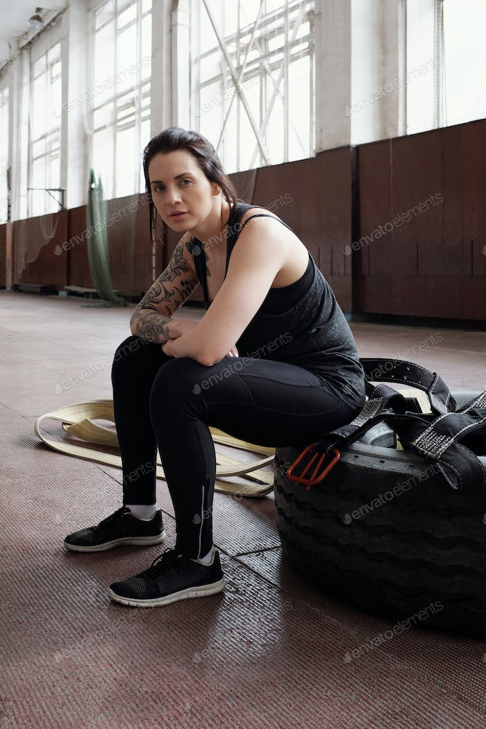 Portrait of young beautiful athletic woman with tattooed arm sitting on tire