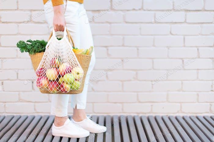 Mädchen mit Mesh-Einkaufstasche voller Äpfel und Strohbeutel mit Bio-Gemüse, Ziegel