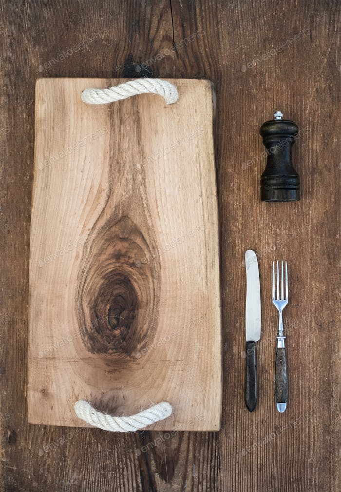 Kitchen-ware set. Old rustic serving board tray, knive and fork, pepperbox