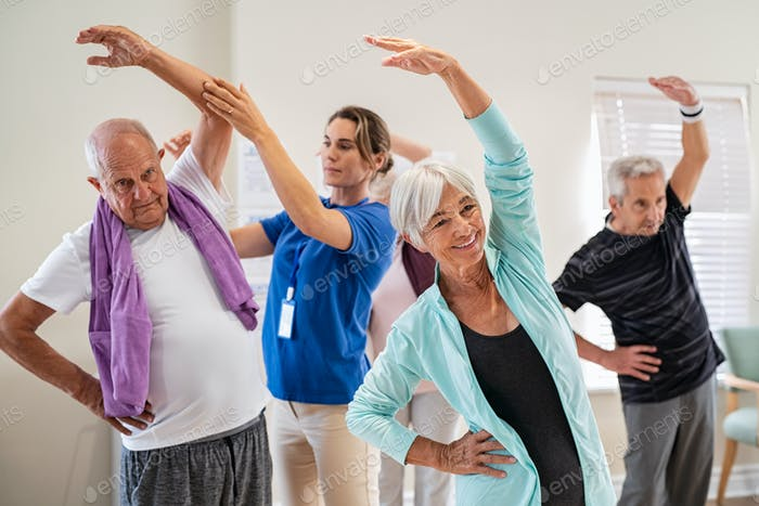 Personas mayores que se estiran con el entrenador en la comunidad de jubilación