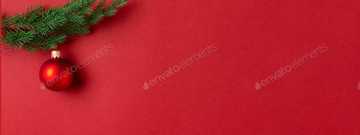 Evergreen Branch with Red Christmas Ball on Red Background.