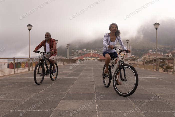 Front view of happy senior couple riding bicycle on promenade at beach with city in the background