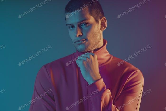 Studio close-up portrait of attractive male model. Color flash studio light