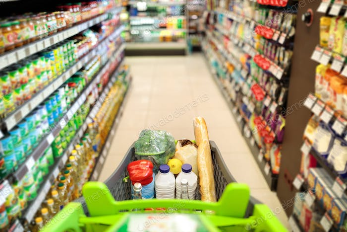 Shopping Cart Full Of Food Products Over Supermarket Aisle Background