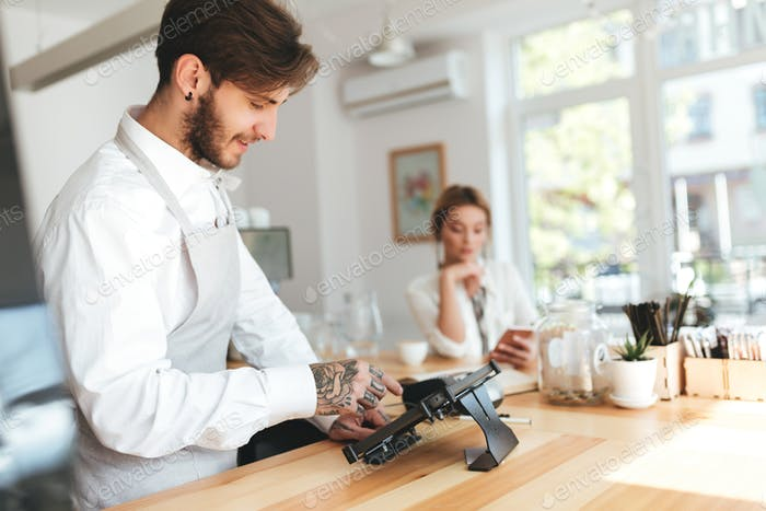 Smiling barista in apron using cash counter while girl at the counter using smartphone