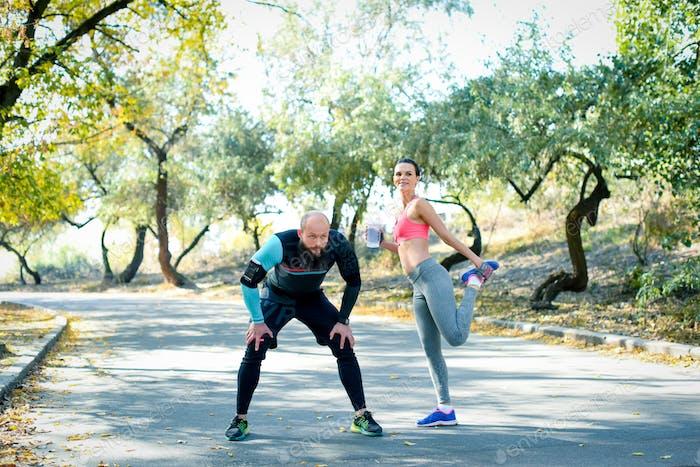 Pareja joven ejercitando y estirando los músculos antes de la actividad Deporte
