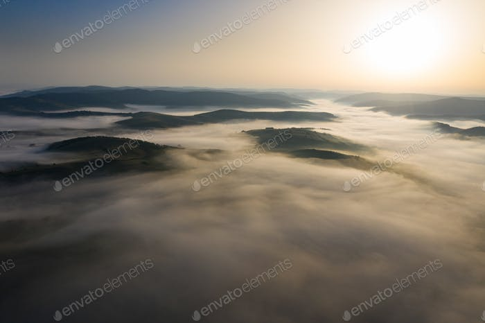 Misty sunrise with sunrays over the hills in Transylvania, Roman