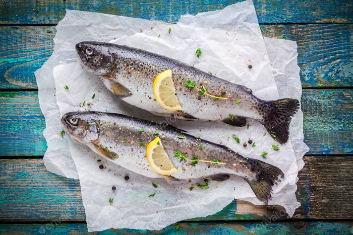 two raw trouts on paper with thyme and lemon  slices