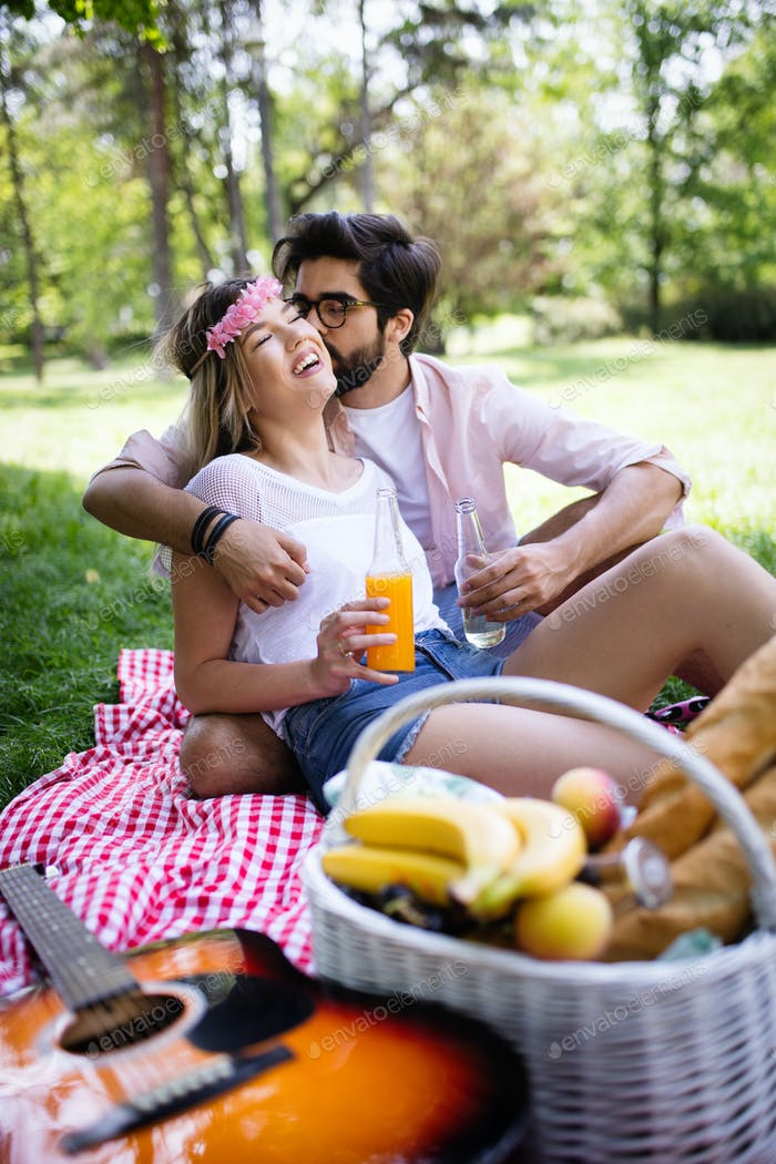 Happy young couple enjoying a picnic in the park together