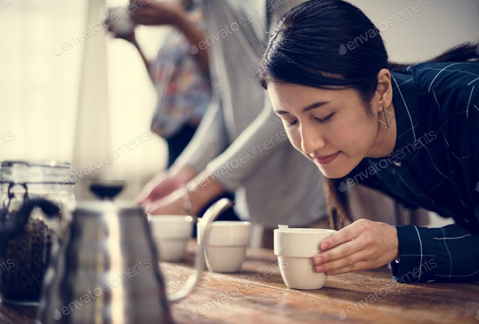 Woman smelling the aroma of a cup of coffee