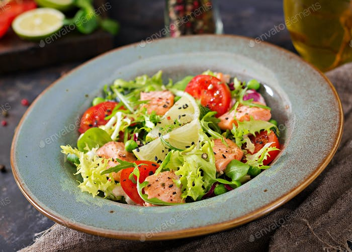 Healthy salad with fish. Baked salmon, tomatoes, lime and lettuce. Healthy dinner.