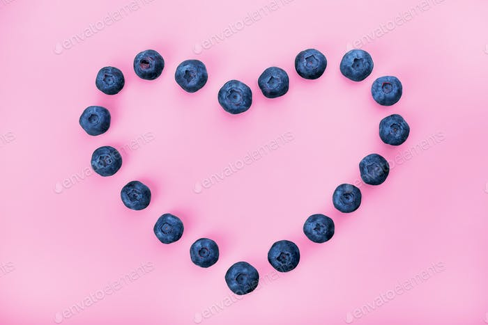 Heart-shaped blueberry berry on a pink background