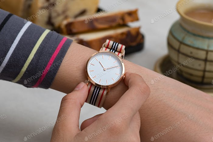 Wrist watches on girl's hand at the coffee break