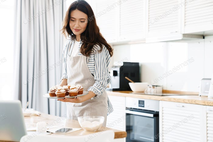 Image of pleased brunette woman smiling and holding muffins