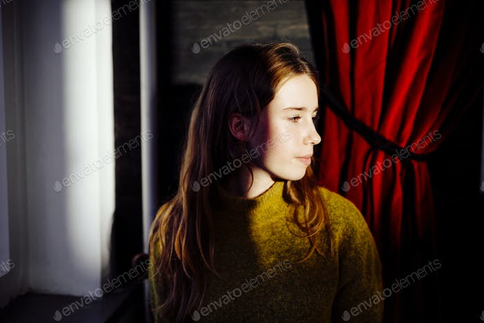Beautiful young woman looking away indoors