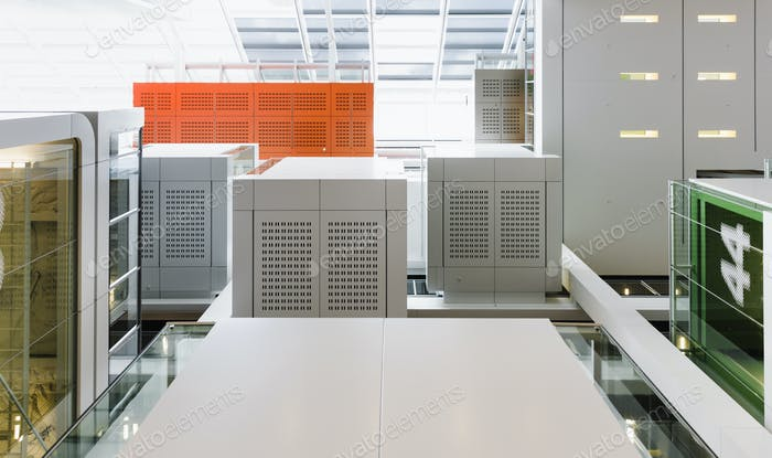 A room with glass cases, computer housing, vents, nad containers. An industrial or office interior.
