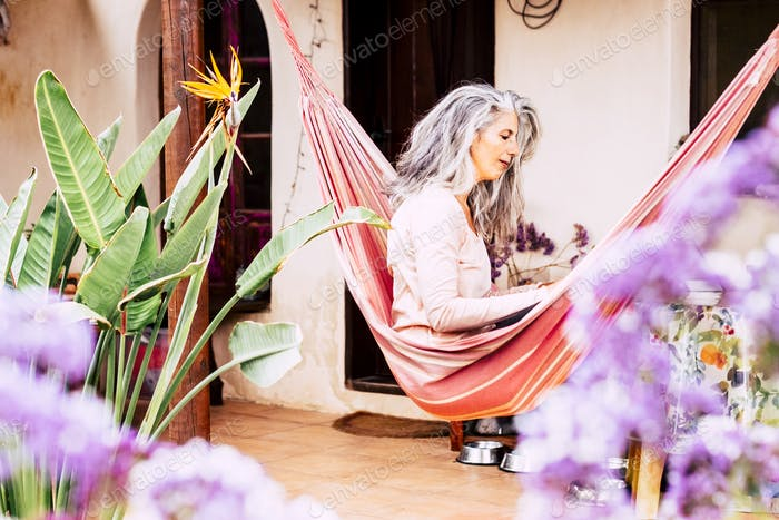 Long grey and white hair adult woman outdoor at home